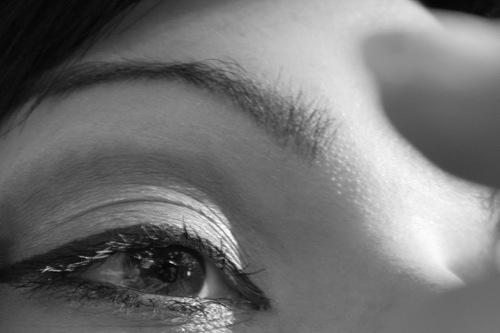 Isabella schminkend mit Handspiegel   Detail: Auge und Stirn