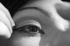 Isabella schminkend mit Handspiegel   Detail: Finger, Auge und Stirn